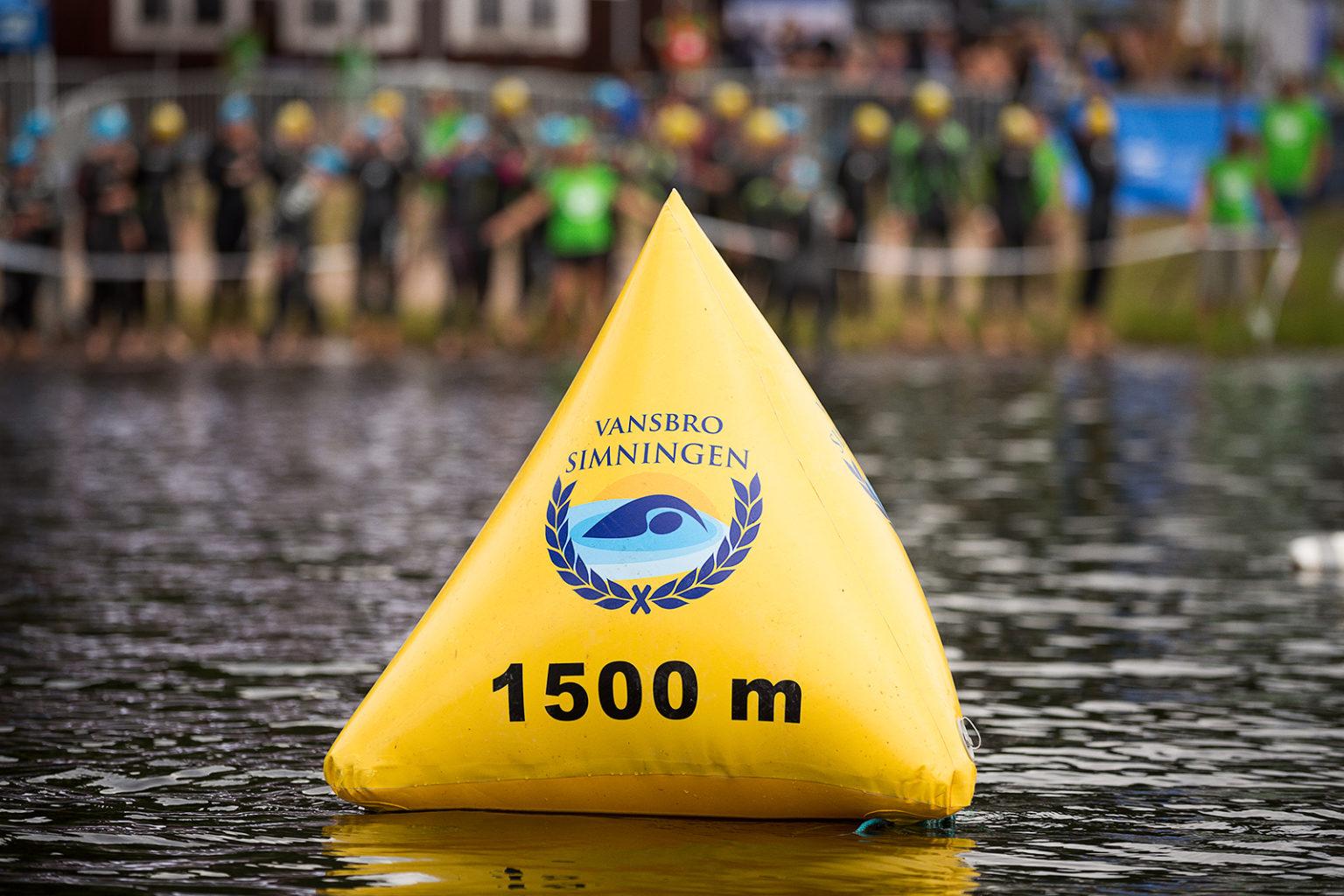 Gul uppblåsbar boj med Vansbrosimningens logotyp och texten 1500 m.