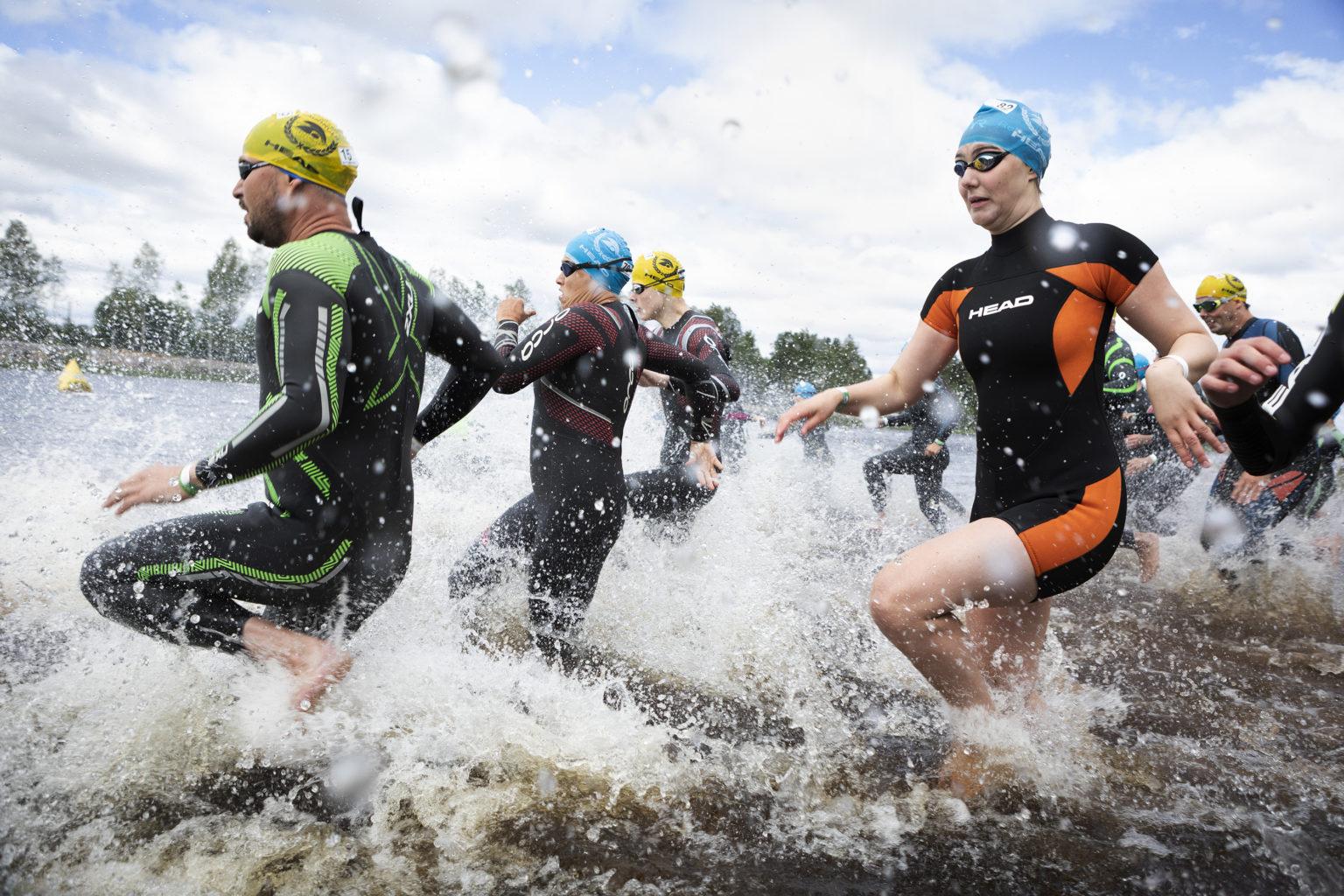 Personer i våtdräkt och badmössor springer i vattnet.