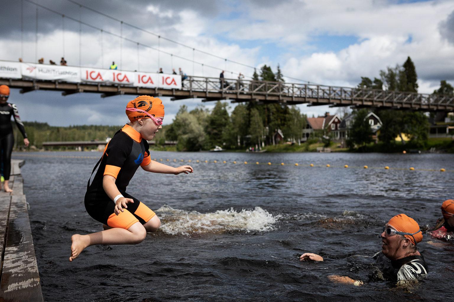 Ung flicka hoppar i vattnet från brygga.