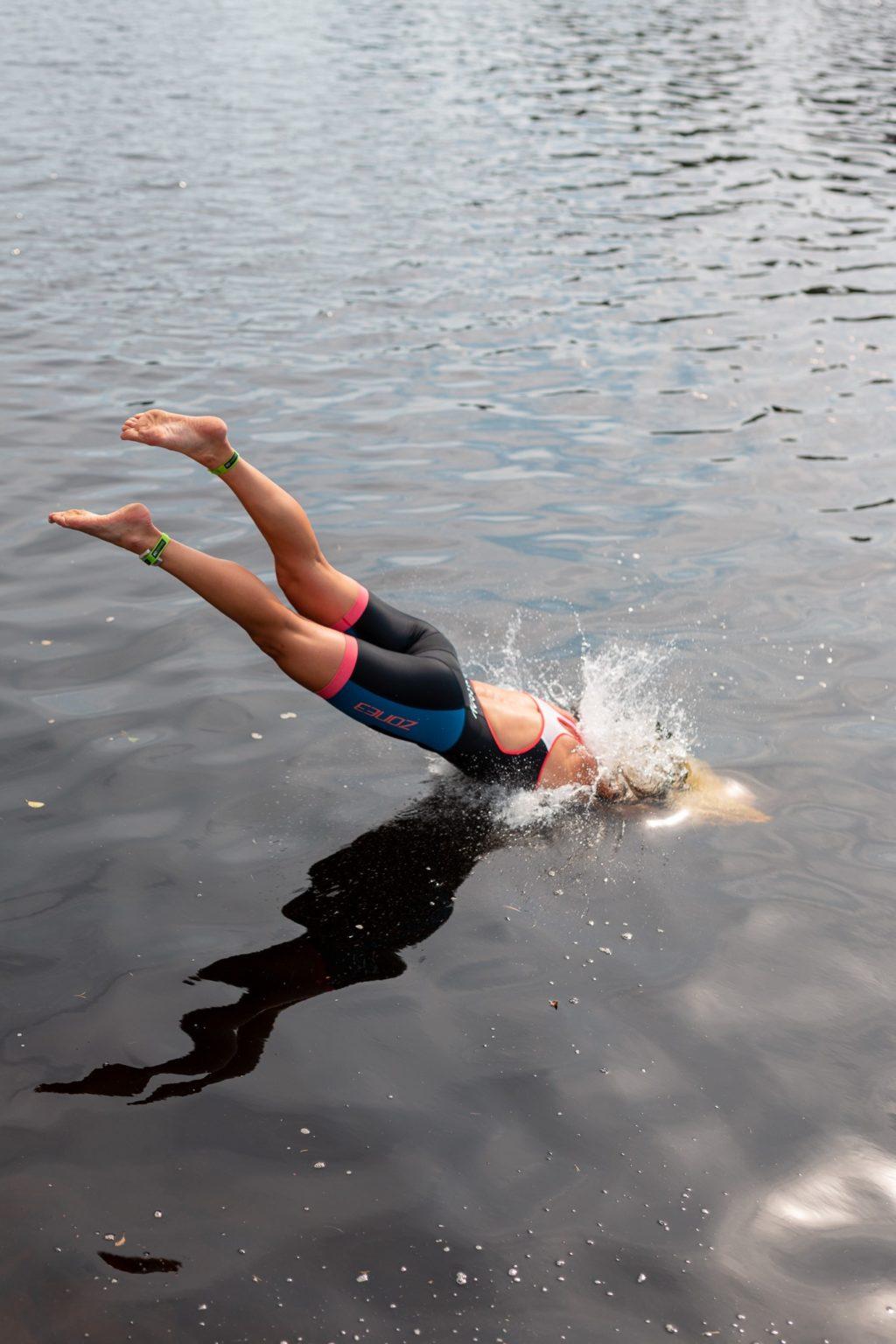 Kvinna dyker i vatten med simkläder.