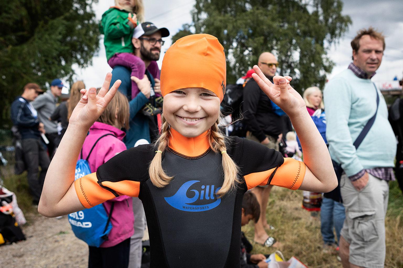 En glad tjej i våtdräkt och orange badmössa.