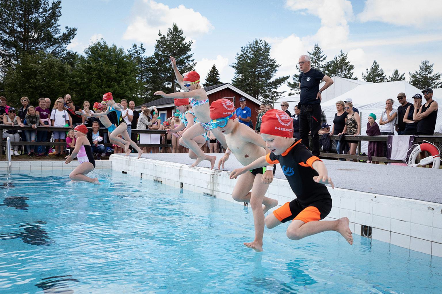 Flera barn hoppar i en pool från kanten.